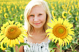 Young blonde green-eyed girl in the field of sunflowers