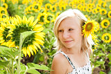 Dreamy cute young girl in the field of sunflowers