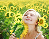 Young girl in the field of sunflowers enjoy a summer day