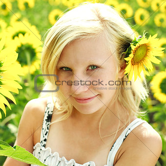 Beautiful portrait of summer young girl in the field of sunflowe
