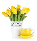 Yellow tulips and tea cup