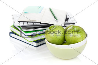 Green apples in fruit bowl and office supplies