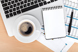 Coffee cup, laptop and notepad over papers with numbers and char
