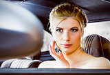 young woman looking in rear view mirror car