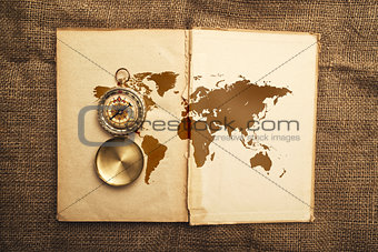 Old open book with compass and world map