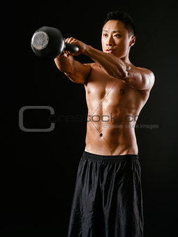 Asian man lifting a kettle bell