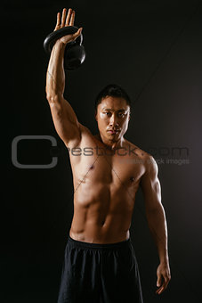 Asian man working out with kettle bell