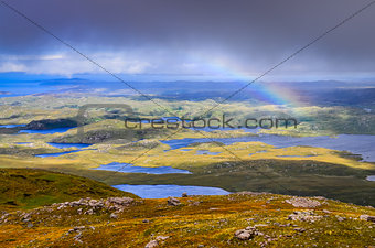 Scenic view of beautiful lakes, clouds and rainbow in Inverpolly