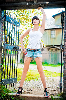 Girl posing in the gate of the old house.