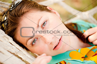 Portrait of a young girl lying in a hammock