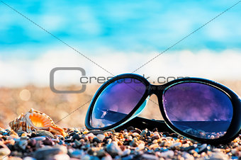 Sunglasses and shells lie on the shingle beach sea