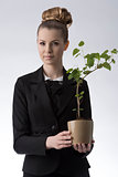 pretty business woman holding money plant