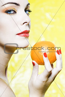 Woman portrait showing a orange tangerine fruit