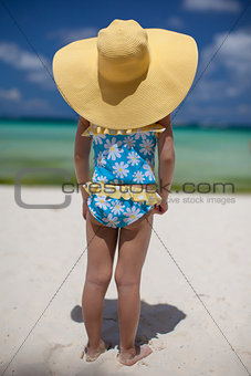 baby girl in her sun hat on the beach