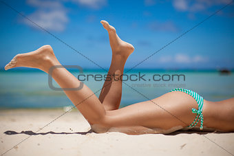 Women's beautiful legs on the beach