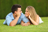 Couple in love dating and looking each other lying on the grass