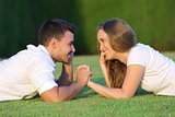 Couple flirting and looking each other lying on the grass