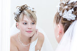 young bride looks into a big mirror