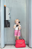 child talking the phone in the airport