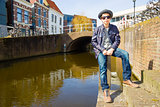 Cute teenage boy in hat (full-length portrait) against canal background