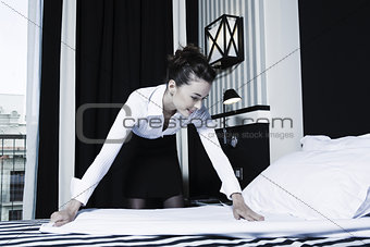 Woman housekeeper doing bed in a hotel bedroom