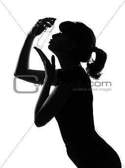 silhouette woman kissing her perfume