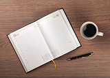 Notepad and coffee cup on wood table