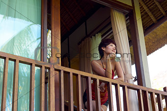 young woman drink coffee on balcony