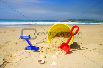 Child's beach bucket and spade on a sandy beach with seashells