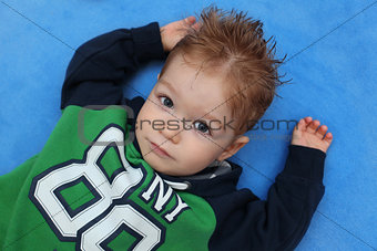 Portrait of little boy lying on floor