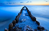 old breakwater in North sea in dusk