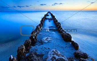 old breakwater in North sea in dusk
