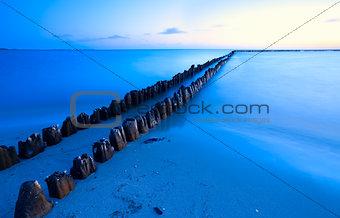 old breakwater in sea with long exposure
