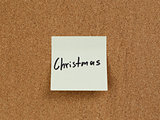 christmas reminder note on cork board