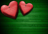 Red Wooden Hearts on Green Wood Background
