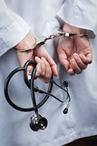 Female Doctor or Nurse In Handcuffs Holding Stethoscope