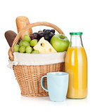 Picnic basket with bread, fruits and orange juice bottle