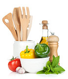 Fresh ripe vegetables, condiments and kitchen utensils