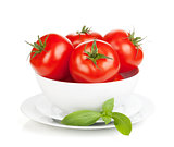 Ripe tomatoes in bowl and basil