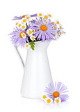 Colorful camomile flowers in jug