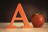 The letter A with an apple on table