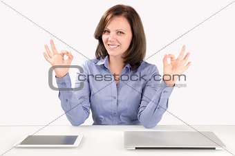 Business woman is sitting in front of a laptop and a tablet