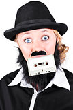 Woman In Male Costume Holding Cassette In Mouth