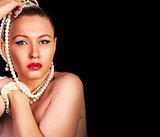 Fashion portrait of a woman with pearls on black background