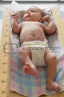 Cute baby lying in height meter