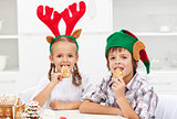 Kids with christmas hats eating gingerbread cookies