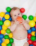Chubby baby girl playing with colorful balls