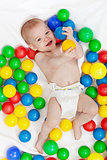Happy baby boy with lots of colorful balls