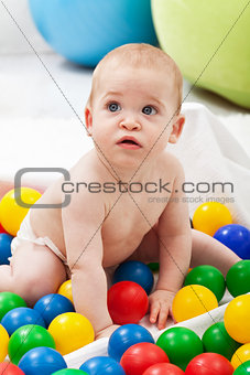 Baby boy playing with colorful plastic balls