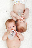 Babies drinking water from feeding bottles